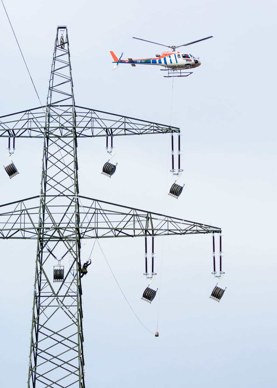 Monteur auf Strommast nimmt Seil von Helikopter an