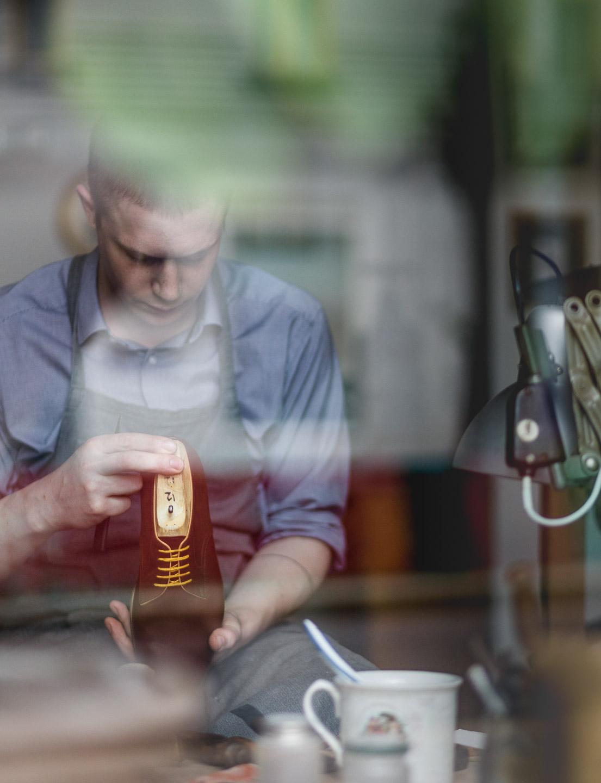 Portrait Schuhmacher bei der Arbeit durch Fenster
