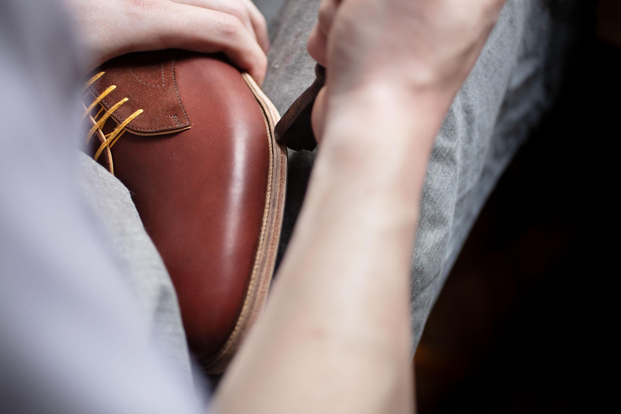 Schuhmacher bearbeitet Maßschuh - Detailaufnahme