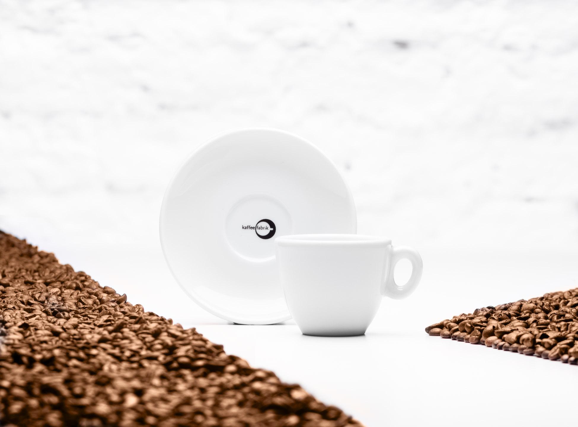 Studioaufnahme einer Kaffeetasse und Untertasse mit Kaffeebohnen