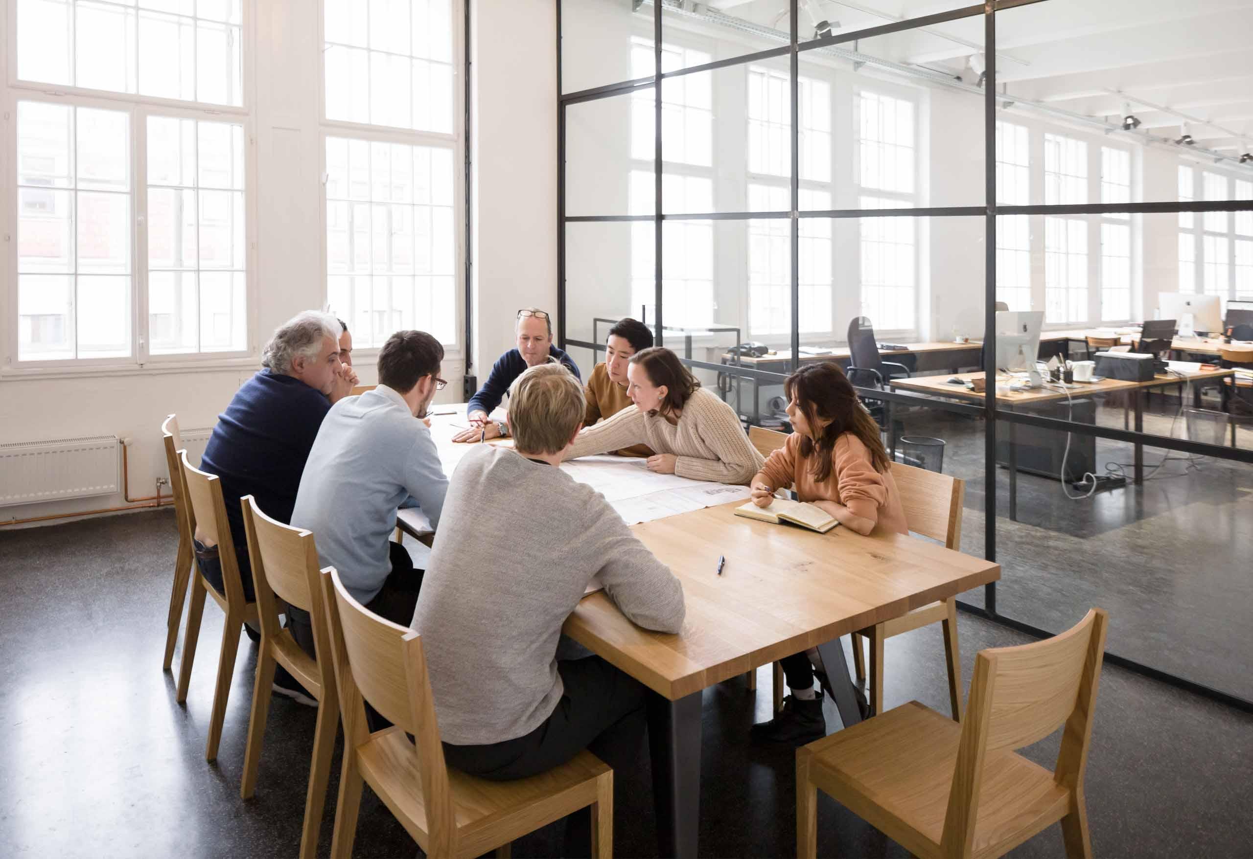 Übersichtsfoto Besprechung an einem großen Tisch in einem Architekturbüro