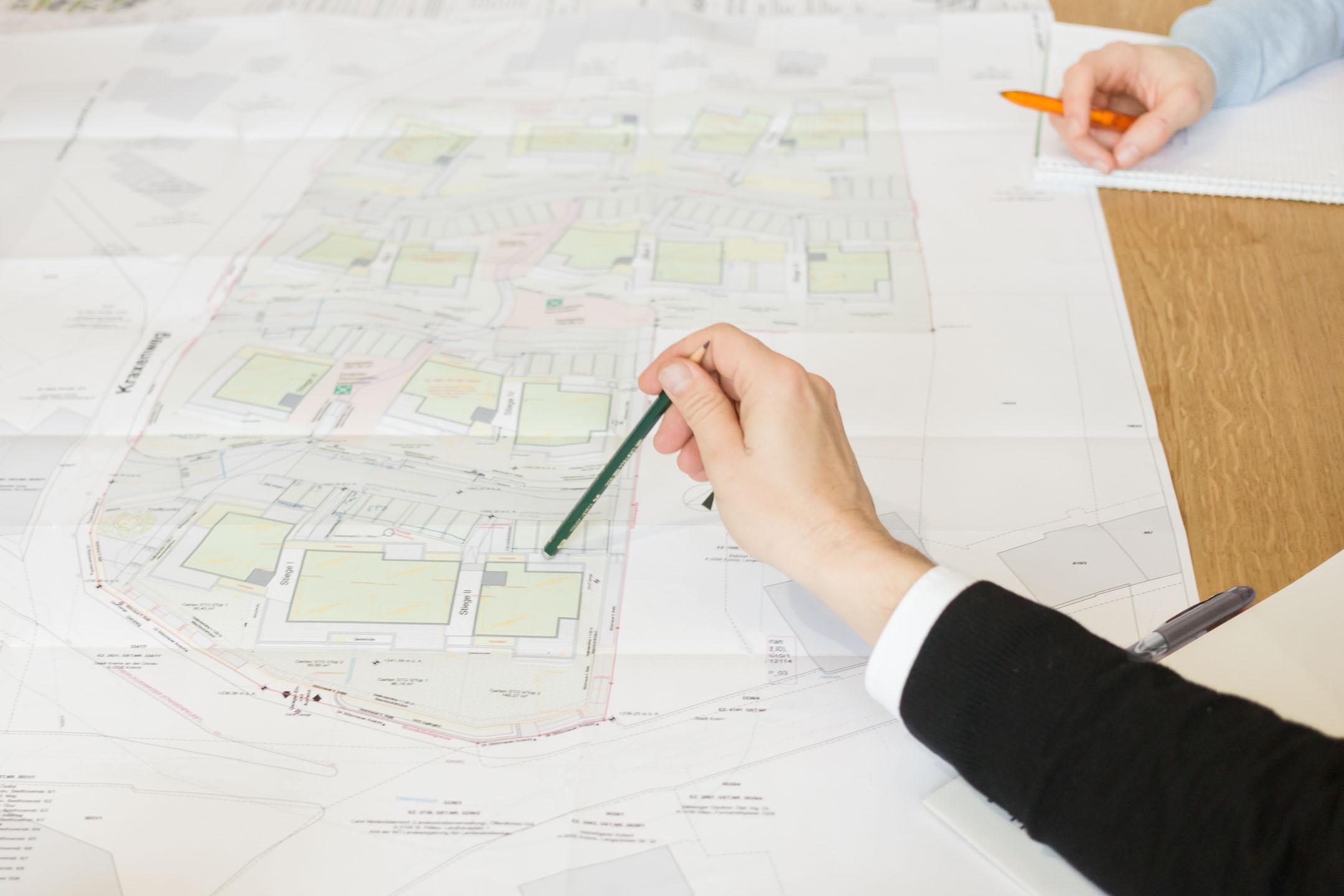 Hand zeigt mir Bleistift auf Detailfoto auf Architektur-Plan